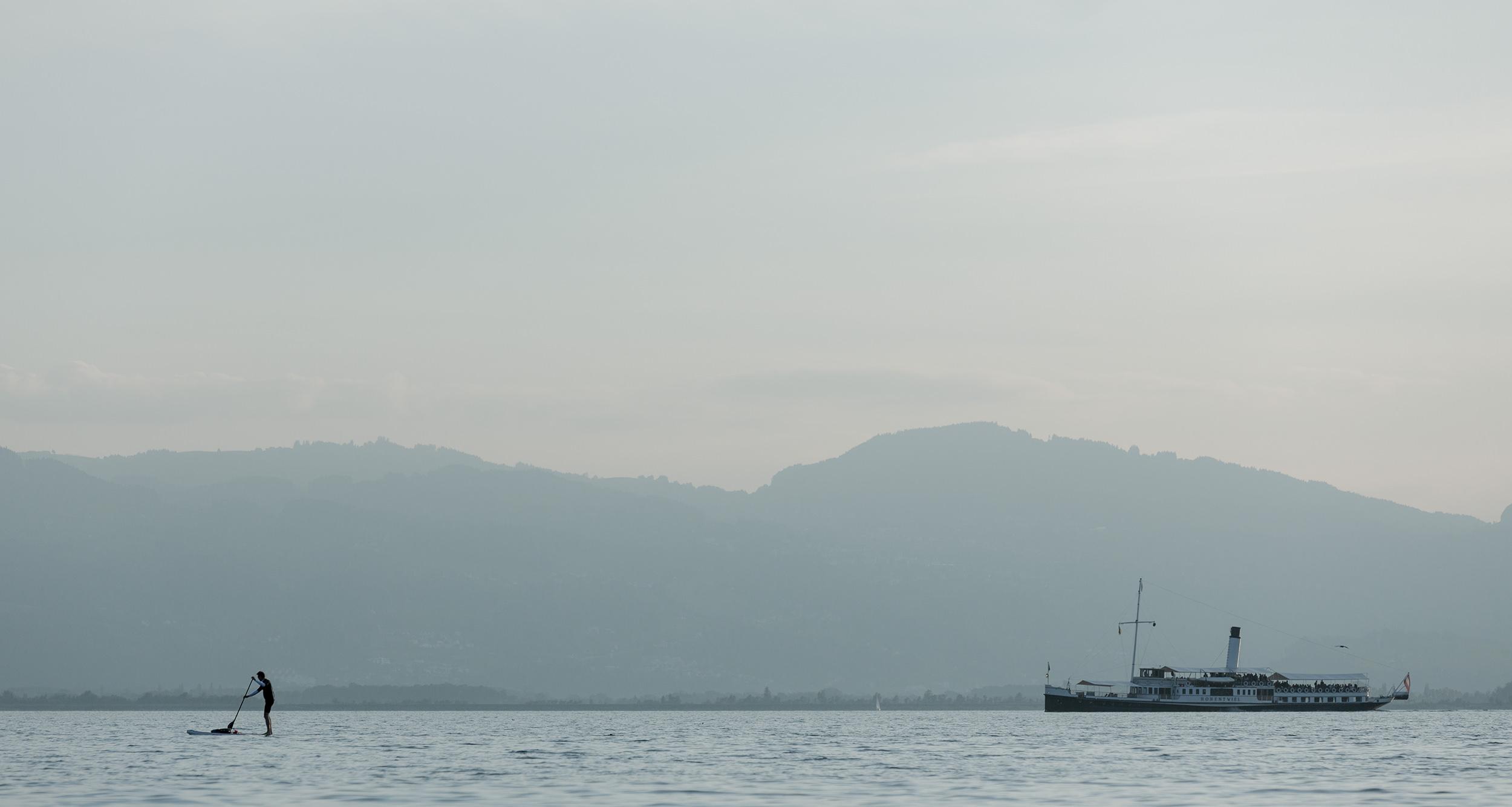 Boot überholt einen Stehpaddler auf dem Bodensee.