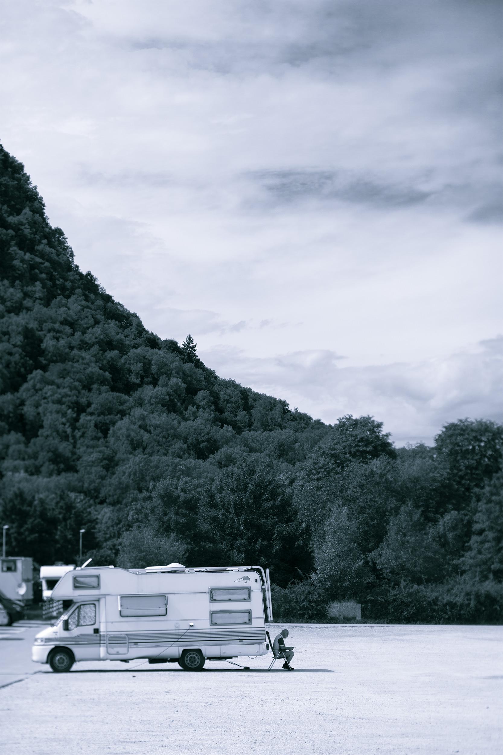Ein Mann sitzt im Schatten seines Campers.