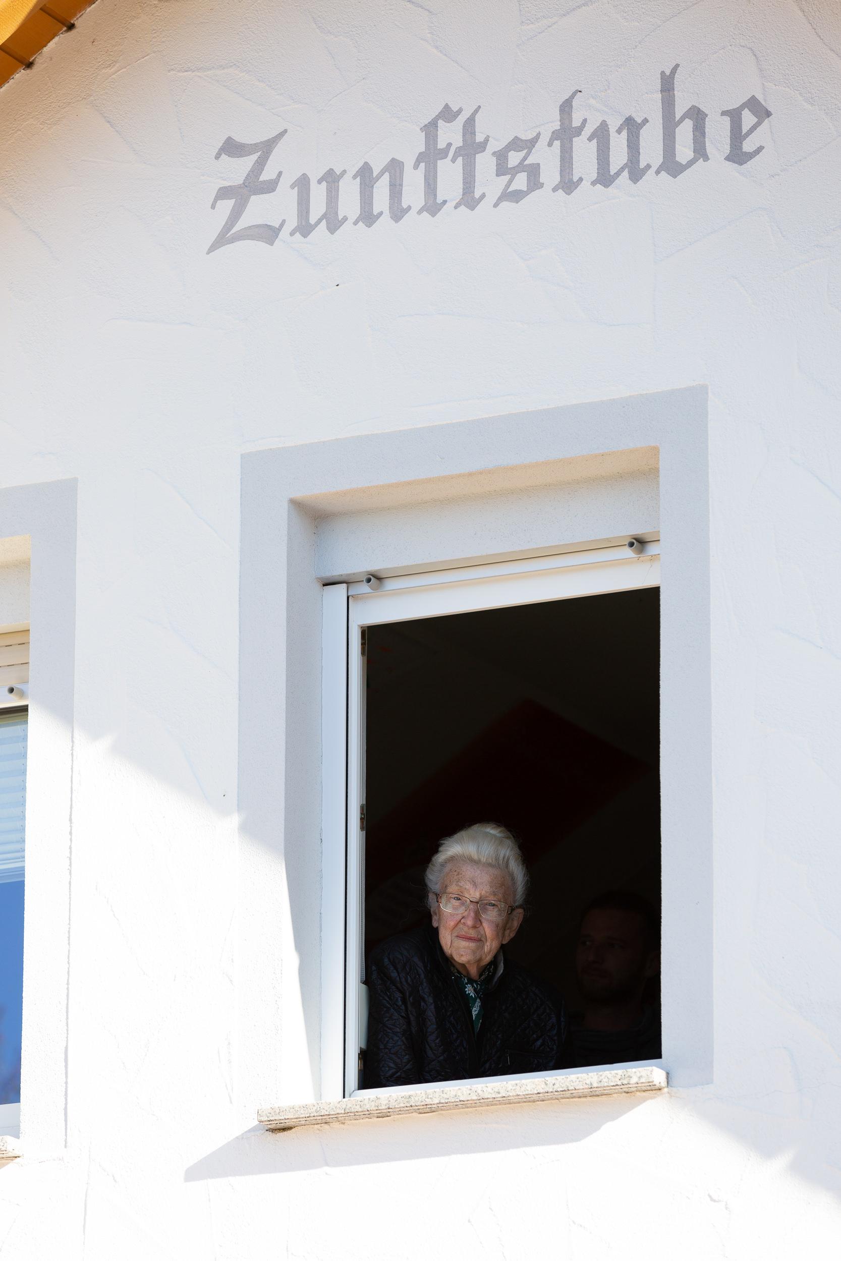 Ältere Frau schaut aus der Zunftstube in Burladingen.