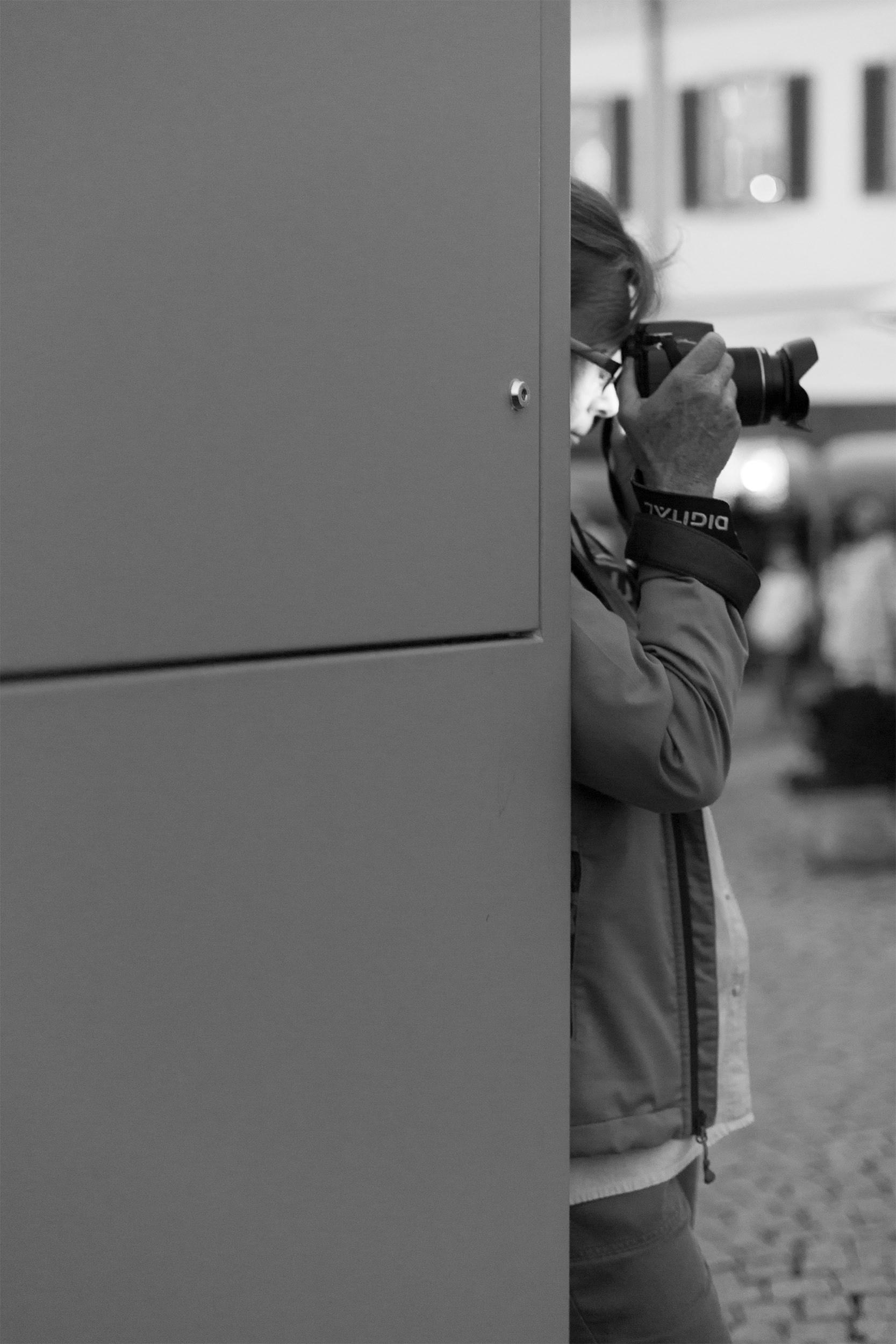 Eine Frau fotografiert an eine Wand gelehnt in Überlingen.