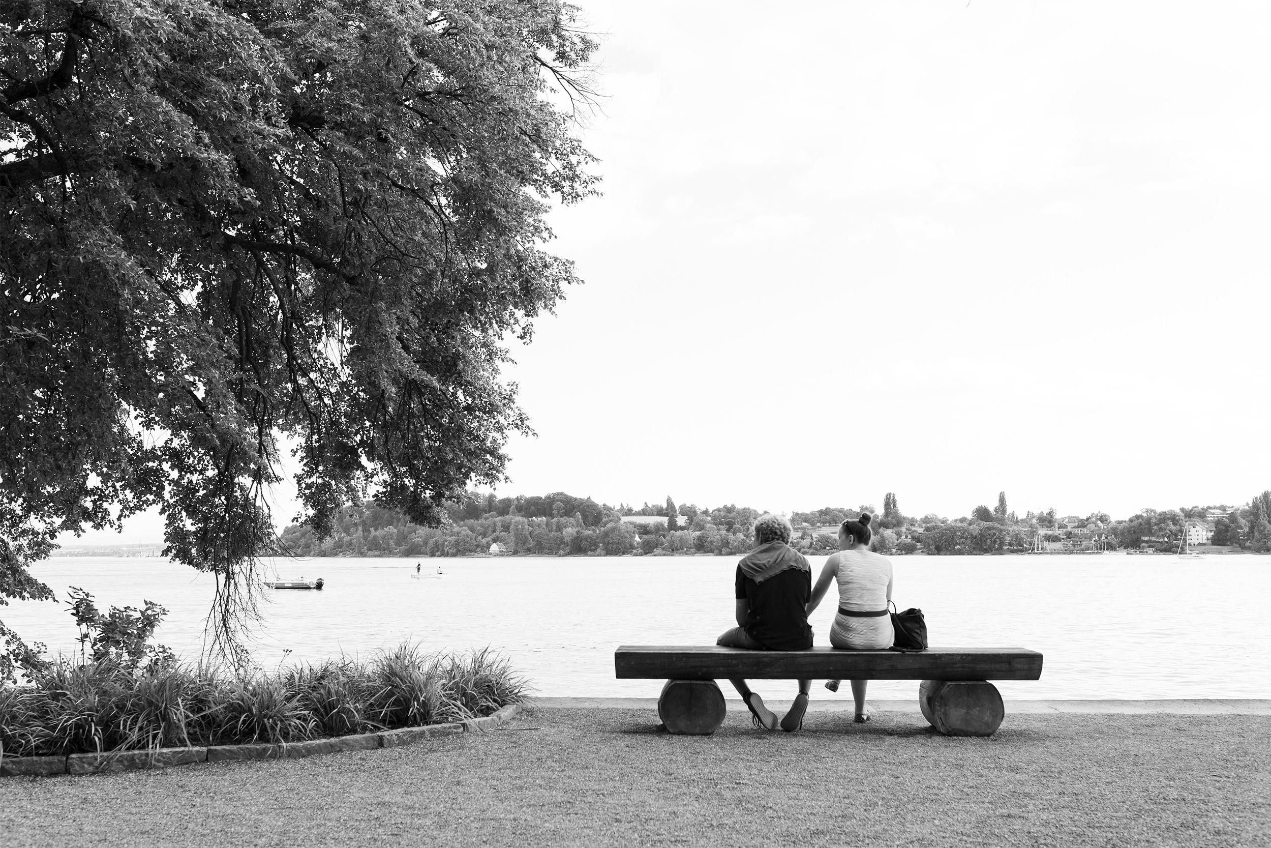 Päärchen sitzt auf einer Bank am Ufer der Insel Mainau, Bodensee.