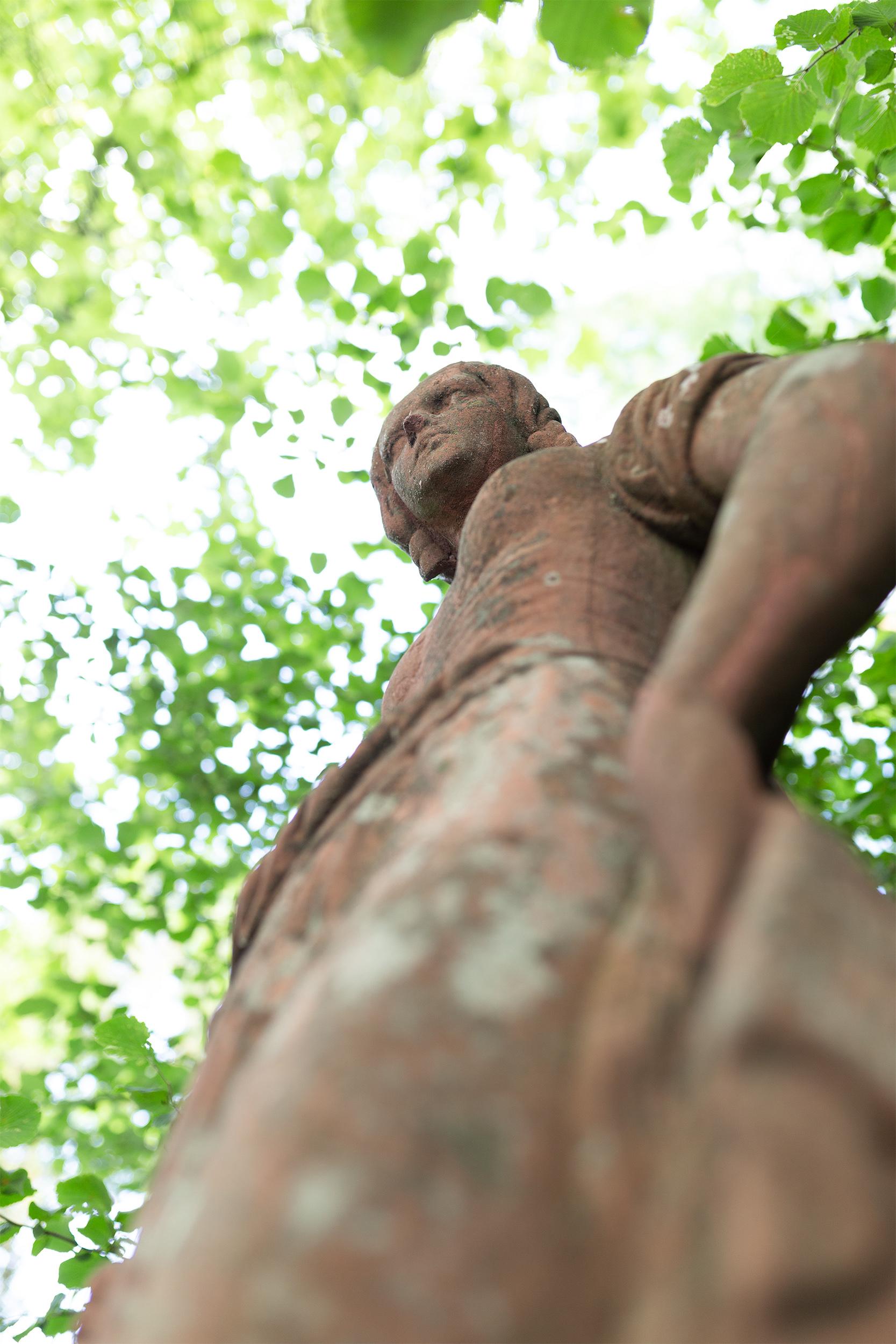 weibliche Steinstatue aus der Froschperspektive.