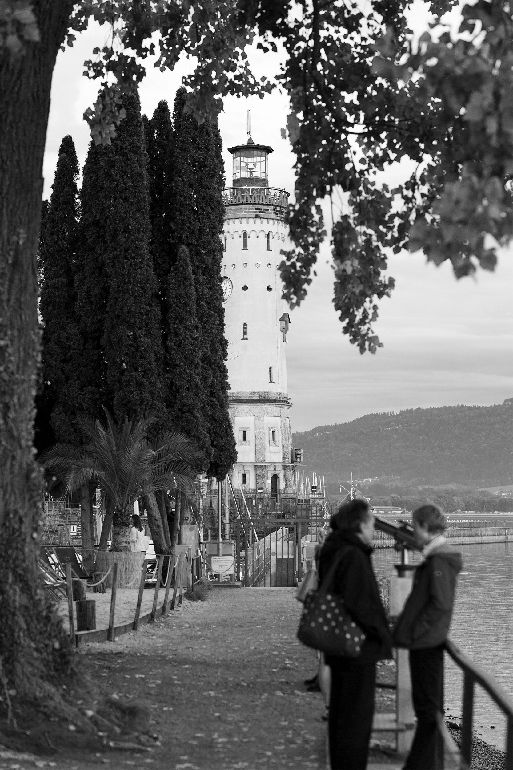 Der Leuchtturm am Lindau Hafen verdeckt von ein paar Bäumen.