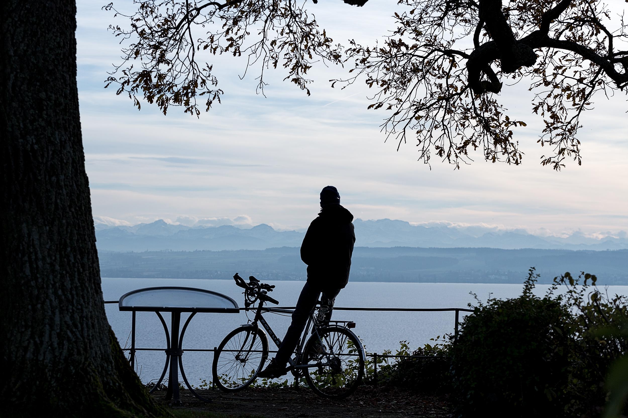 Radfahrer rastet an einem Aussichtspunkt bei Meersburg.