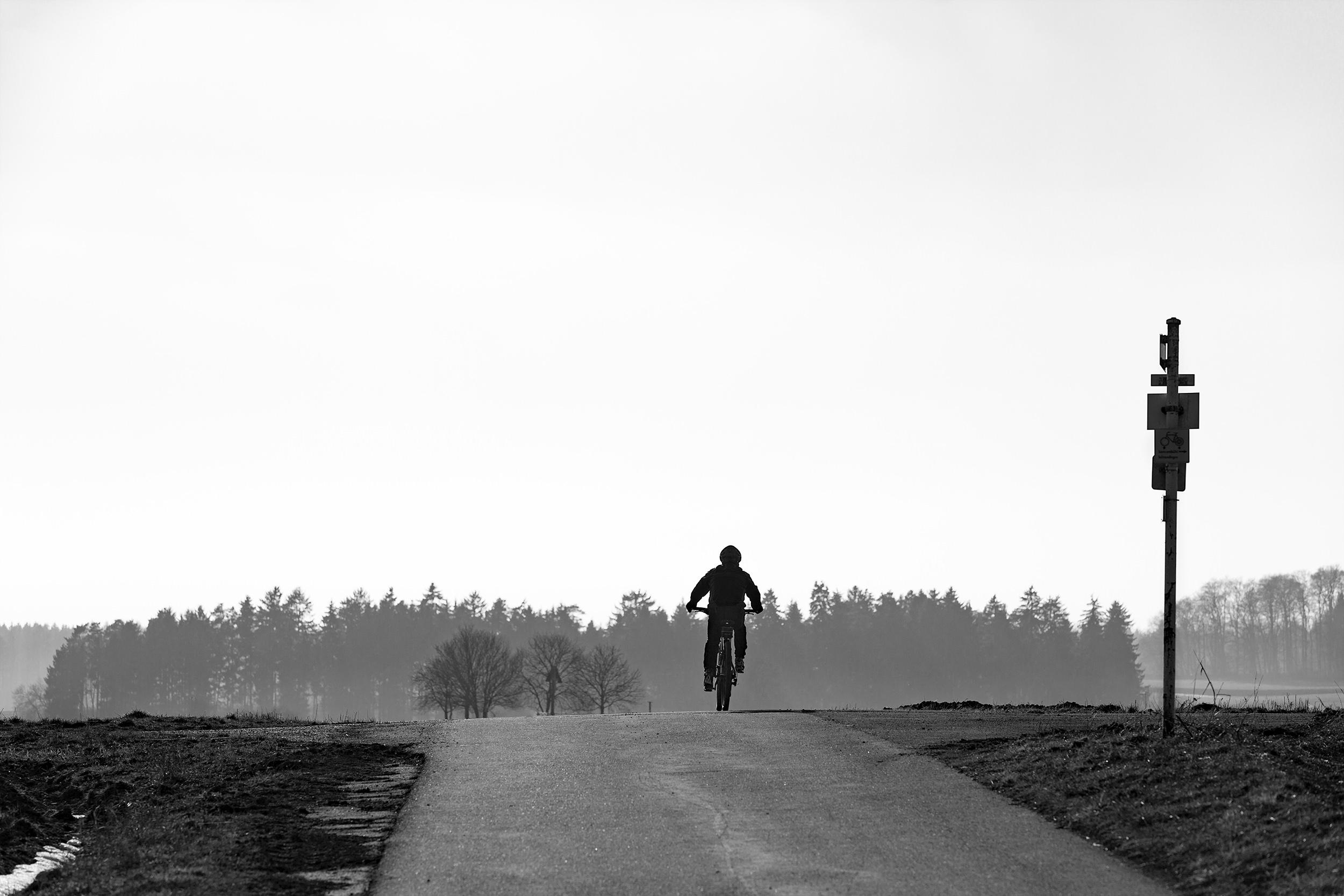 Radfahrer auf Feldweg.