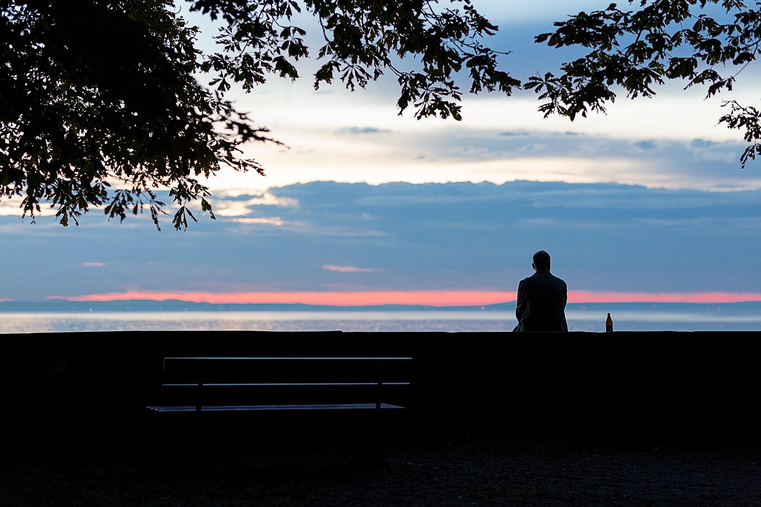 Ein Mann sitzt auf der Ufermauer von der Insel Lindau.