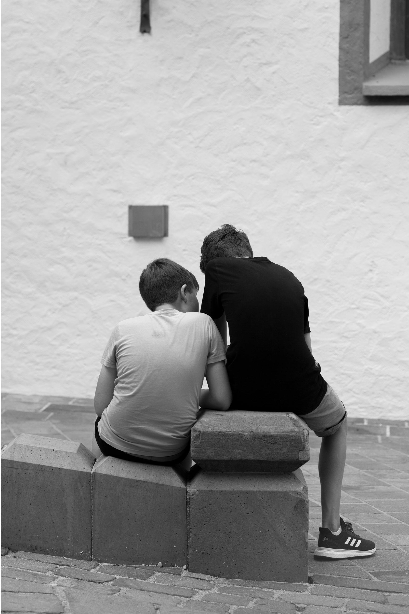 Zwei Kinder sitzen auf einem Stein.