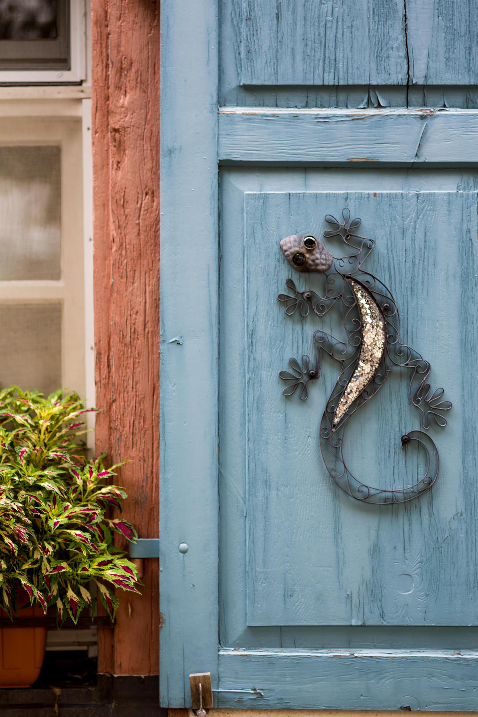 Ein Salamander aus Metall an einem Fensterladen.