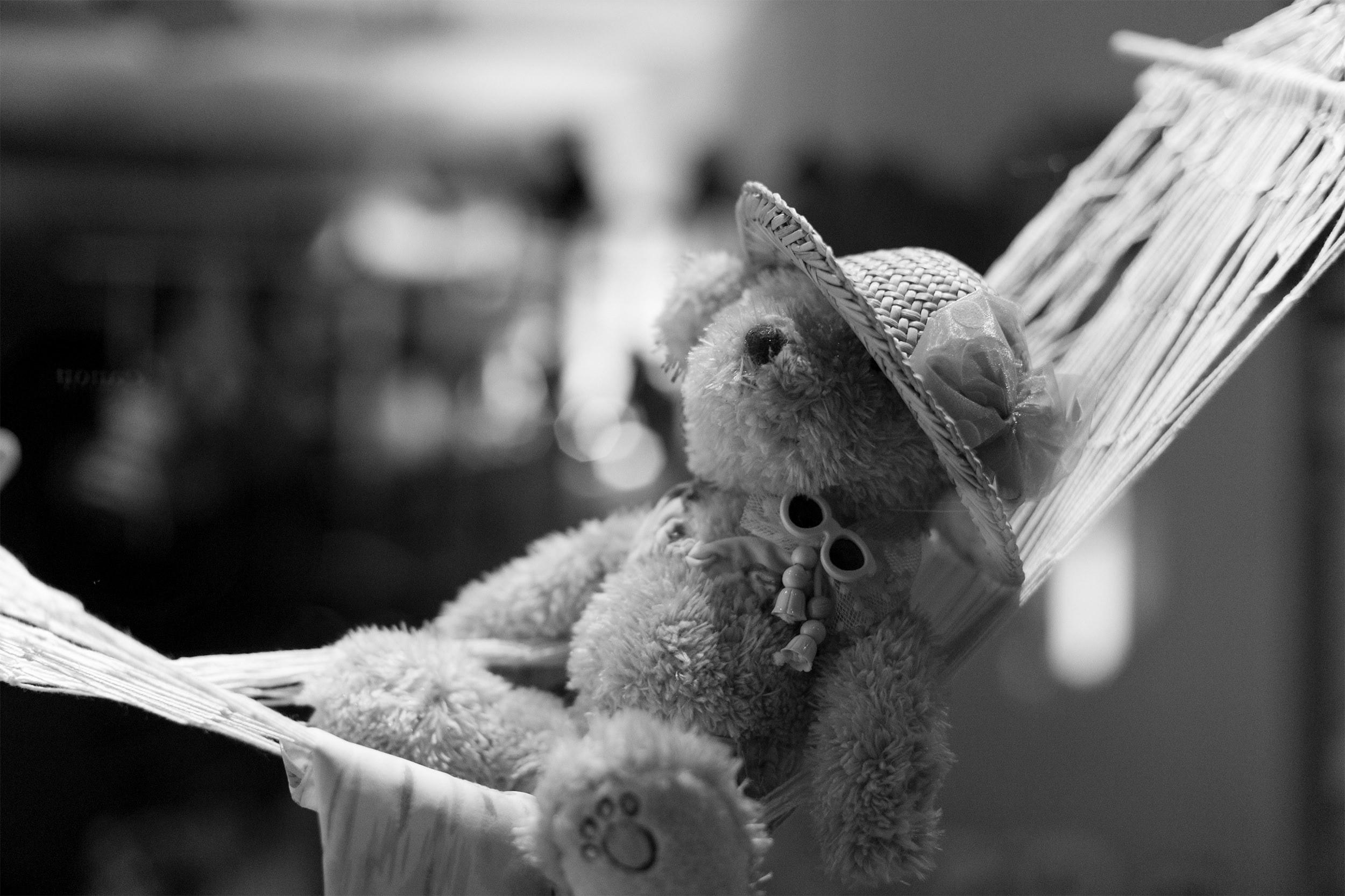 Ein kleiner Plüschteddy relaxed in einer Hängematte.