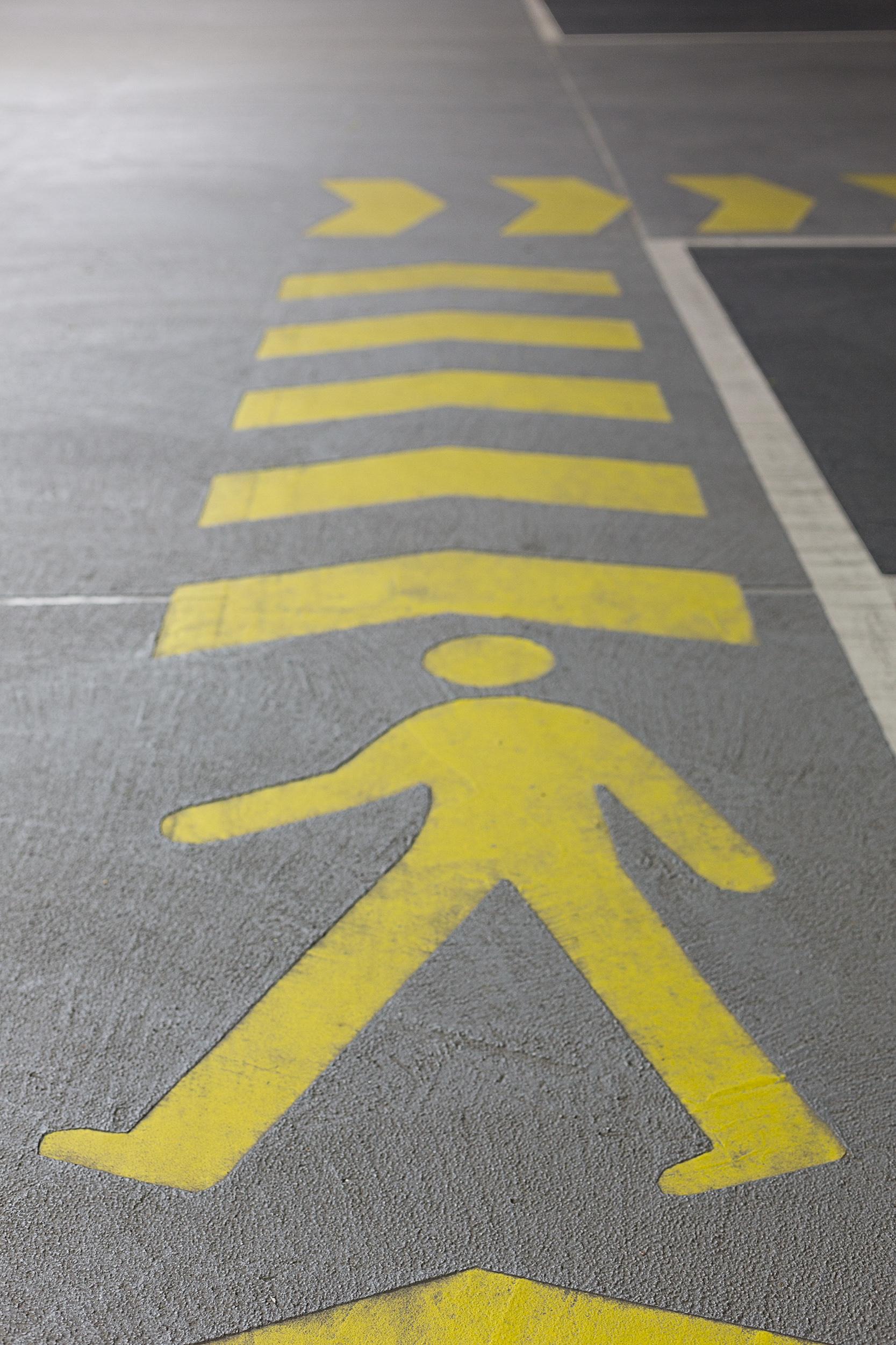 Gelbes Strichmännchen auf dem Betonboden gemalt.