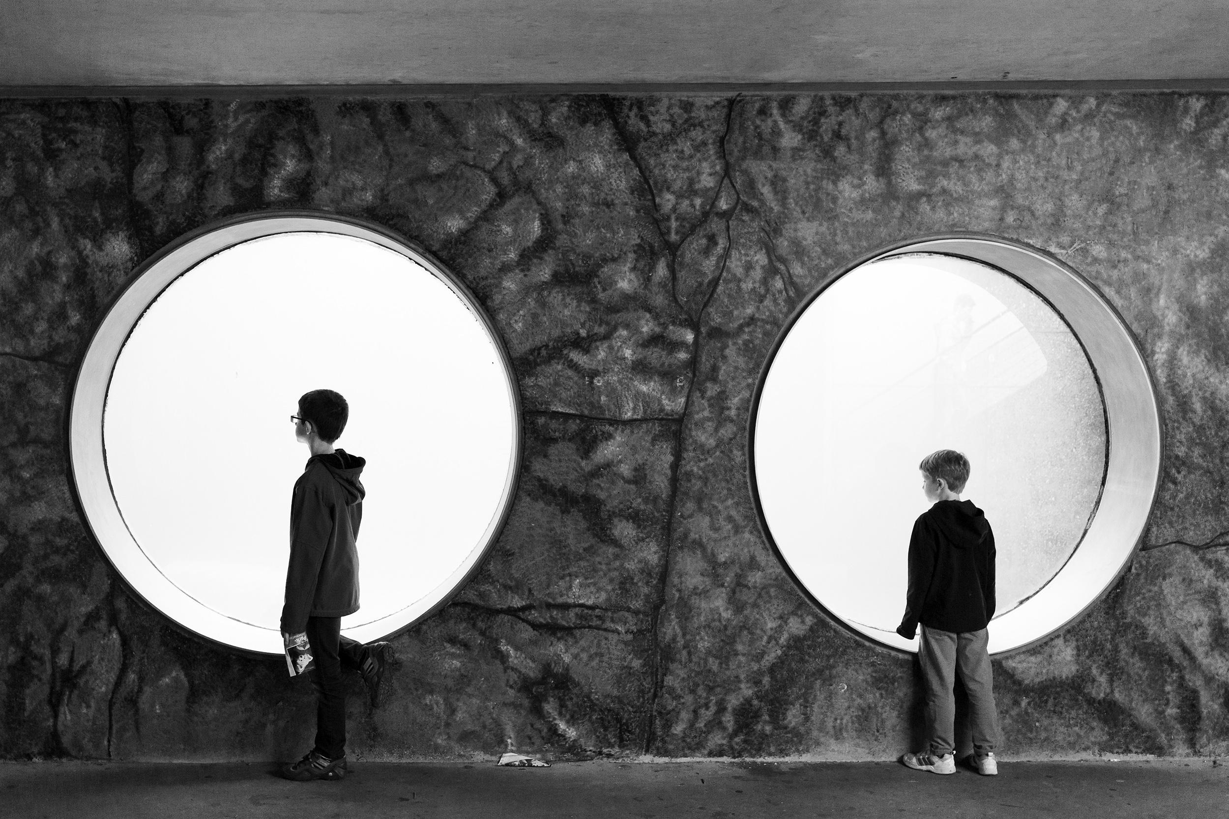 Zwei kleine Kinder schauen durch runde Fenster im Zoo Karlsruhe.