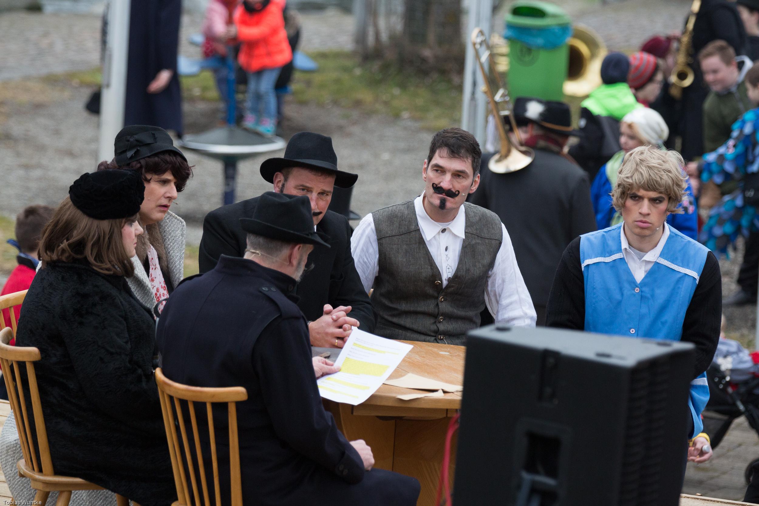 Fasnetsspieler während des Theaterstücks sitzen an einem Tisch.