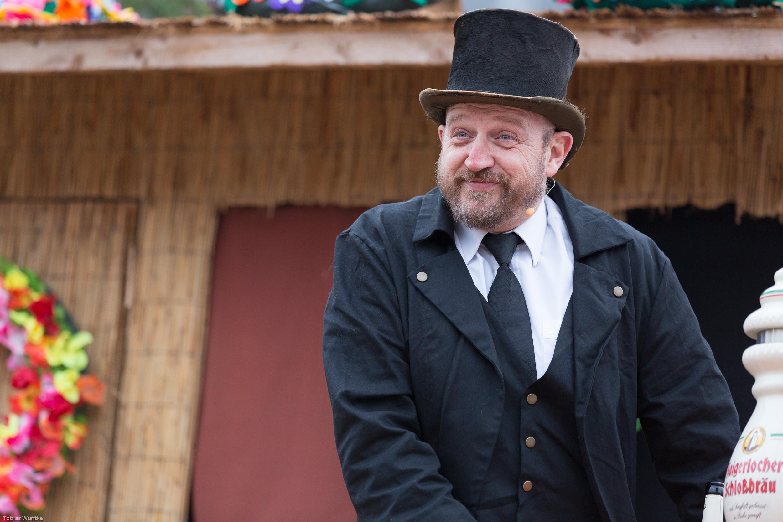 Ein Theaterspieler mit abgewetztem Zylinder und wildem Bart.