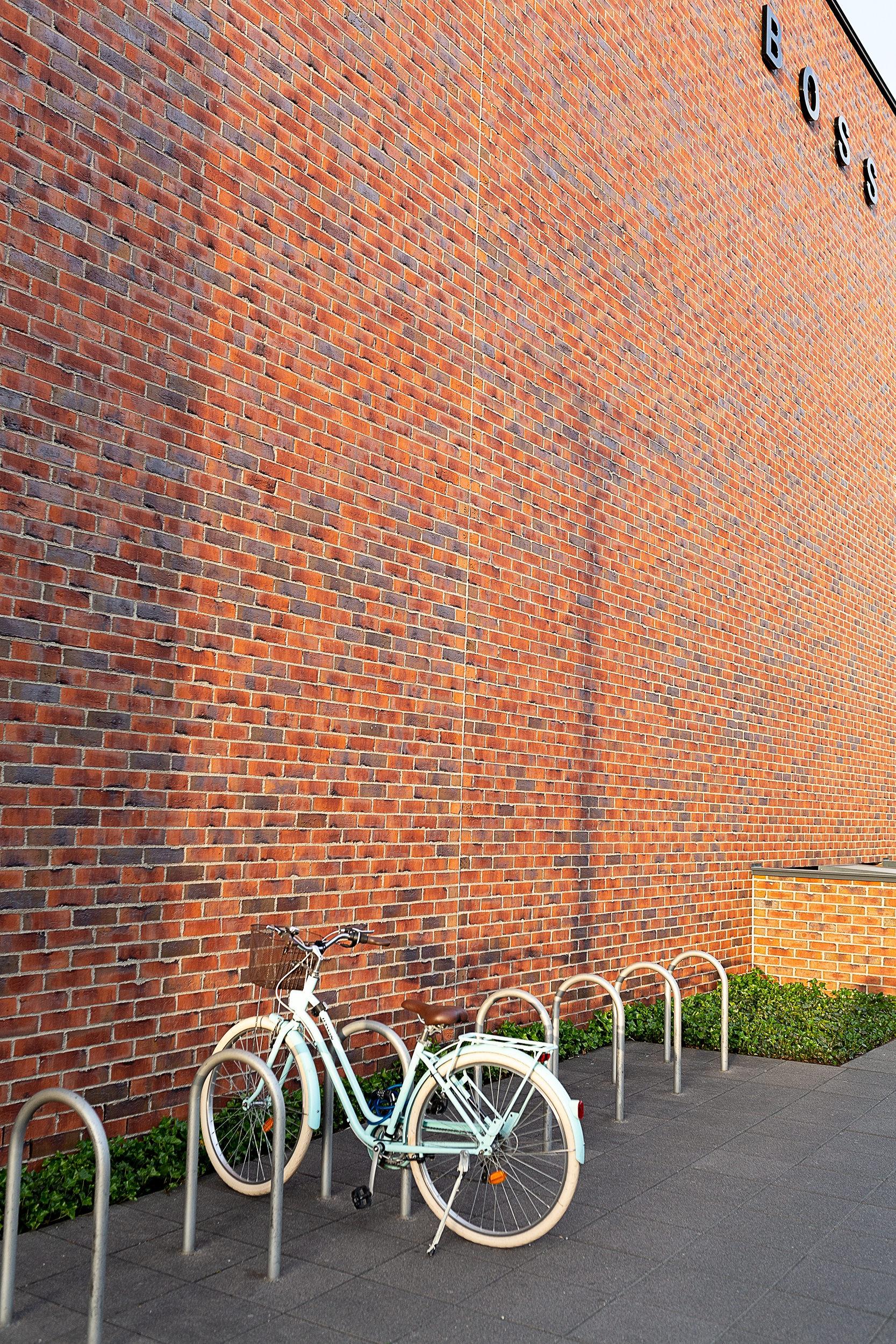 Fahrrad steht vor dem Gebäude des Fabrikverkaufs von Hugo Boss.