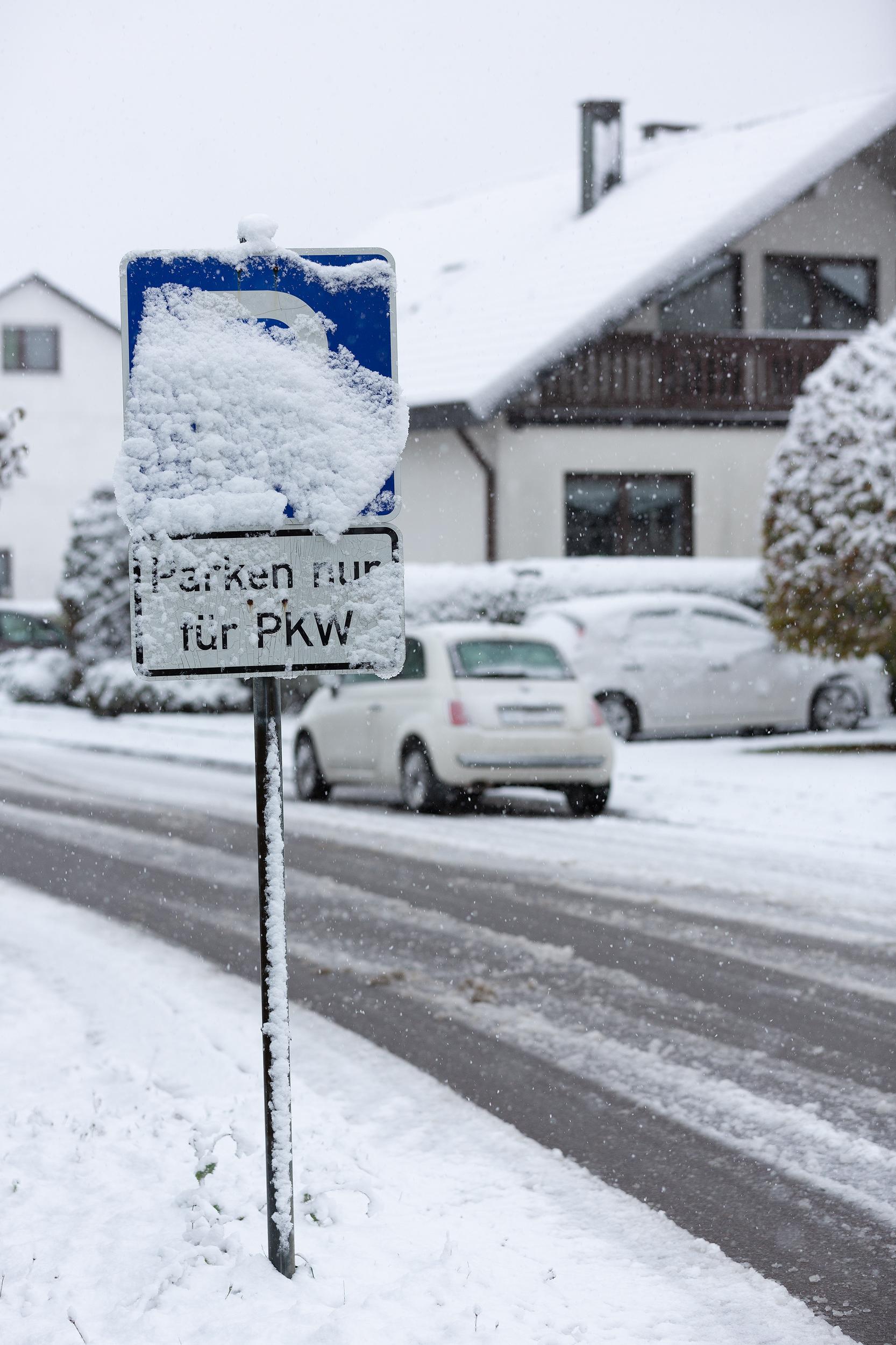 Verschneites Parkplatzschild an einer nicht geräumten Seitenstraße.